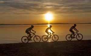 Mountainbiker im Sonnenuntergang am Chiemseestrand in Feldwies
