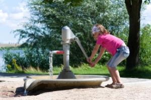 kleines Mädchen spielt im Sommer an einer Wasserpumpe